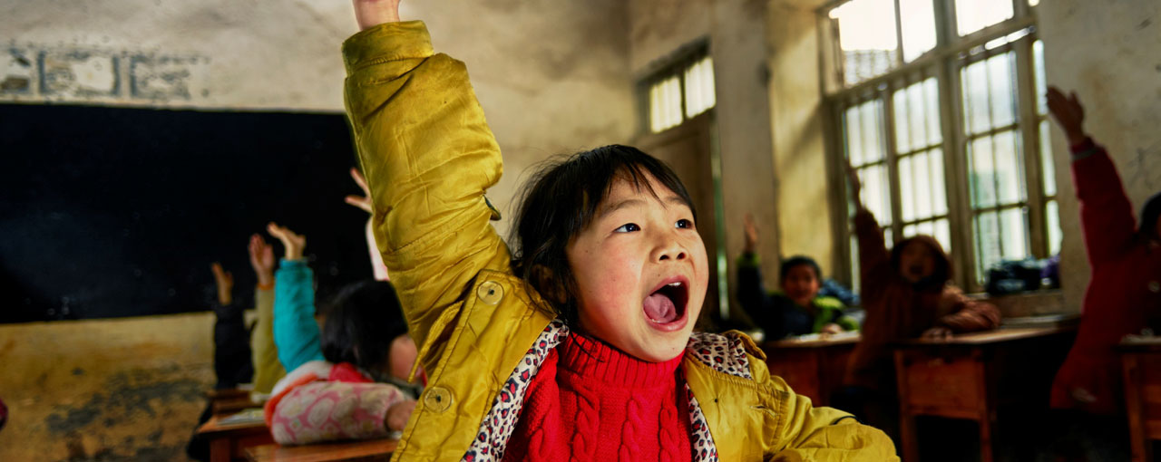 Young girl raising her hand